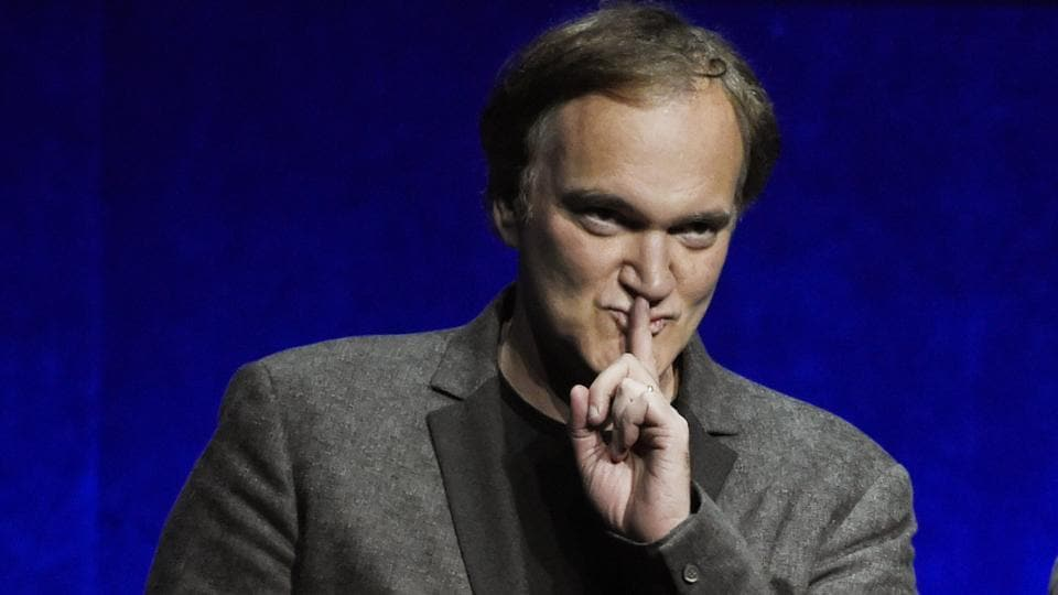 Quentin Tarantino, writer/director of the upcoming film Once Upon a Time in Hollywood, gestures to the audience during the Sony Pictures Entertainment presentation at CinemaCon 2018.