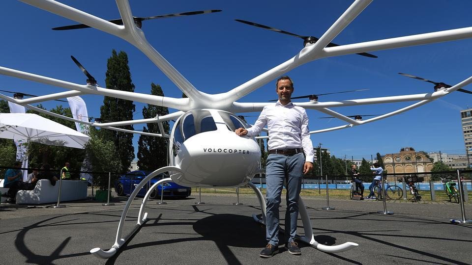 Florian Reuter, chief executive officer of Volocopter GmbH, poses for a photograph beside a Volocopter 2X multi-rotor electric helicopter at the Noah Technology Conference in Berlin, Germany, on Wednesday.