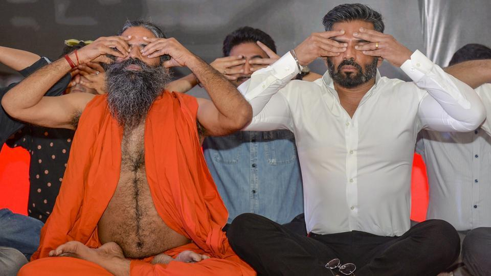 Yoga guru Ramdev and actor Suniel Shetty perform 'yogasana' during the launch of 'Mission Fit India', in New Delhi, on June 04, 2018. (Manvender Vashist / PTI)