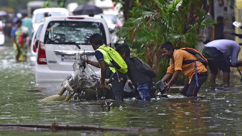 "People push a motorbike through a water-logged street in Mumbai. The advisory released by the IMD read: ""Active to vigorous monsoon conditions are likely to prevail, leading to persistent very heavy rainfall along the west coast, especially between June 10 and 11. In view of intense rainfall forecast, people are advised to abstain from outdoor activities as much as possible."" (Vijayanand Gupta / HT Photo)"