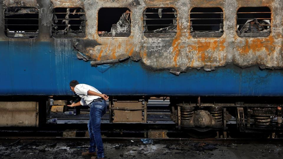 A railway official examines the damaged coach of a passenger train after it caught fire at a railway station in Mumbai on May 29.