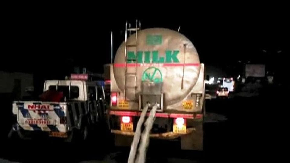Milk is spilt on the road at Khed Shivapur in Pune on June 1.