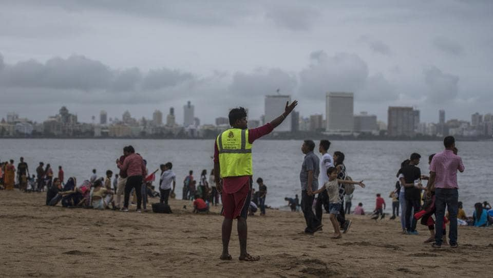 A life guard warns people as high-tide approaches at Girgaon chowpatty. Following the warnings issued by IMD, the Brihanmumbai Municipal Corporation (BMC) cancelled leaves of all senior officials, including deputy municipal commissioners, assistant commissioners and heads of departments as a precautionary measure. (Pratik Chorge / HT Photo)