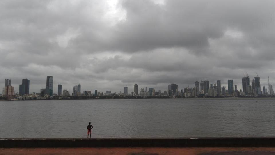A man stands along the sea front as pre-monsoon clouds gather over the Mumbai skyline. While the south-west monsoon made a presence over Goa on Thursday, the weather bureau said that conditions were favourable for monsoon to set in over Maharashtra by Friday and over Mumbai by Saturday. The India Meteorological Department (IMD) has forecast 'extremely heavy rain' over the weekend advising people to stay indoors. (Punit Paranjpe / AFP)