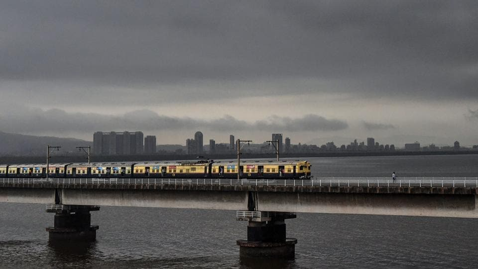 A suburban train runs across a bridge on Vashi creek as dark monsoon clouds hover. Although railway tracks near Sion and Thane were submerged under water, train services largely remained functional with delays reported in the suburban sections of the city. (PTI)