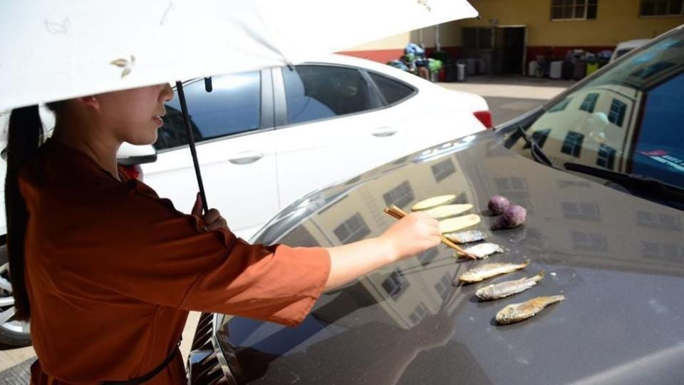 A woman has been photographed frying five small fish and vegetables while sheltering herself from the heat with an umbrella.