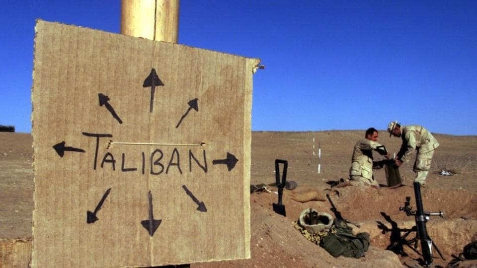 US Marines fill sand bags around their light mortar position on the front lines of the US Marine Corps base in southern Afghanistan. Nearby a cardboard sign reminding everyone that the Taliban forces could be anywhere and everywhere.
