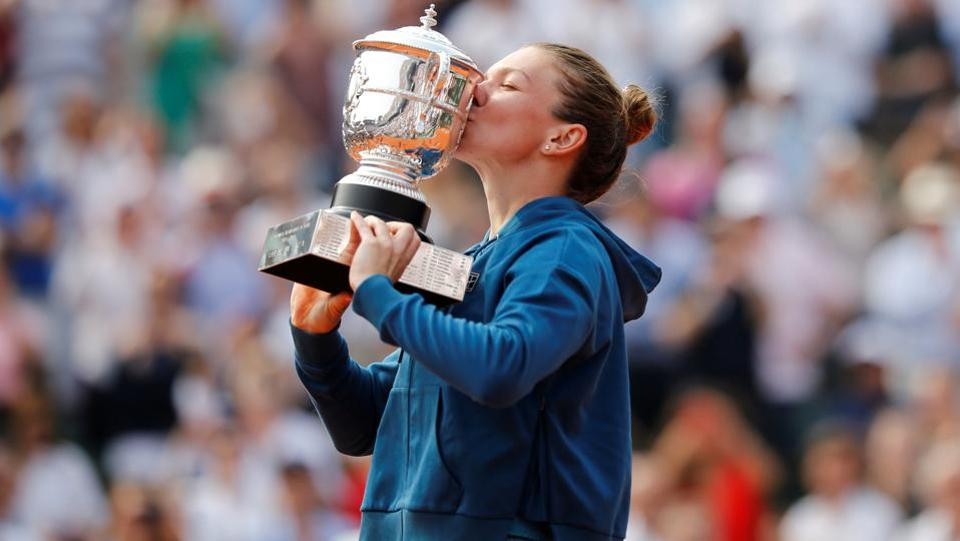 Halep celebrates by kissing the trophy.  (REUTERS)