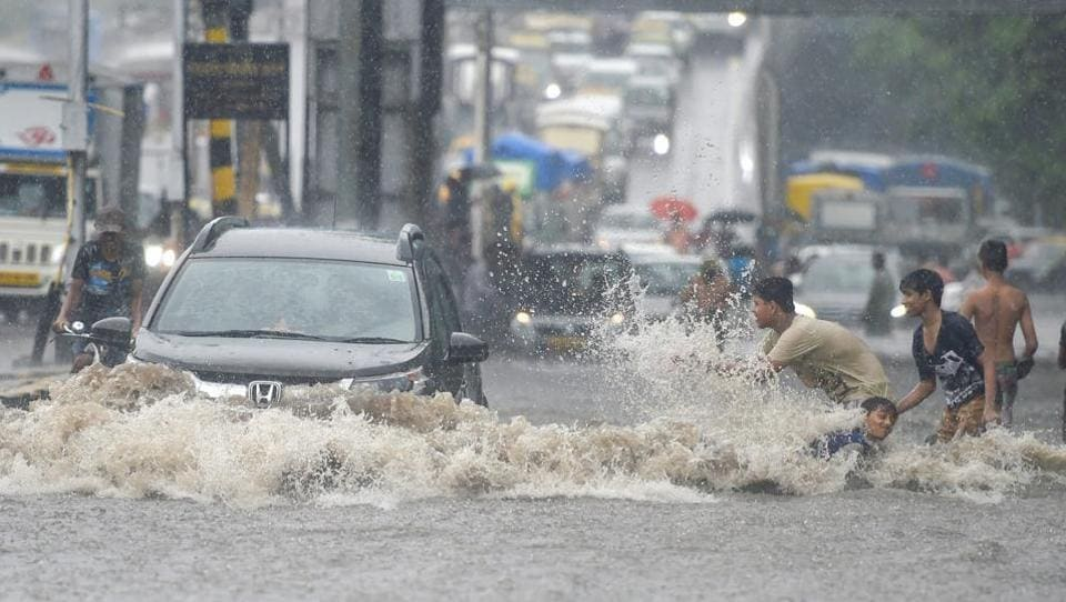 Vehicles wade through a waterlogged street at King Circle after heavy rains in Mumbai. The monsoon officially arrived in Mumbai on Saturday and hit the city and other parts of Maharashtra, disrupting flights, the suburban train system and road traffic, besides claiming two lives. (Shashank Parade / PTI)