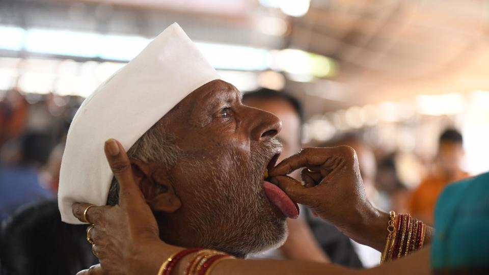 A member of the Bathini Goud family administers 'fish medicine' to a patient at the exhibition ground in Hyderabad, Telangana on June 8, 2018. The medicine, to patients since 1840 as a cure for asthma and other breathing disorders, is placed in the mouth of a live murrel fish and then slipped into the mouth of the patient. (Noah Seelam / AFP)
