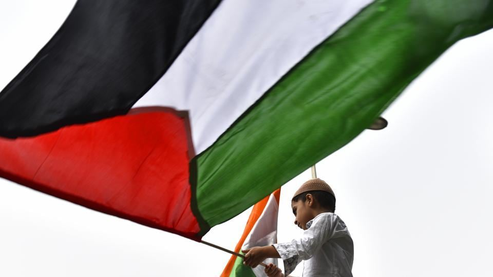 A boy hurls Palestine flag as members of Majlis-e-Ulama-e-Hind protest against the illegal occupation of Israel on Holy Al-Aqsa Mosque, the relocation of US Embassy from Tel Aviv to Jerusalem and the atrocities being conducted by Israel against innocent people, at Jantar Mantar in New Delhi, on June 8, 2018. (Sanchit Khanna/HT PHOTO)