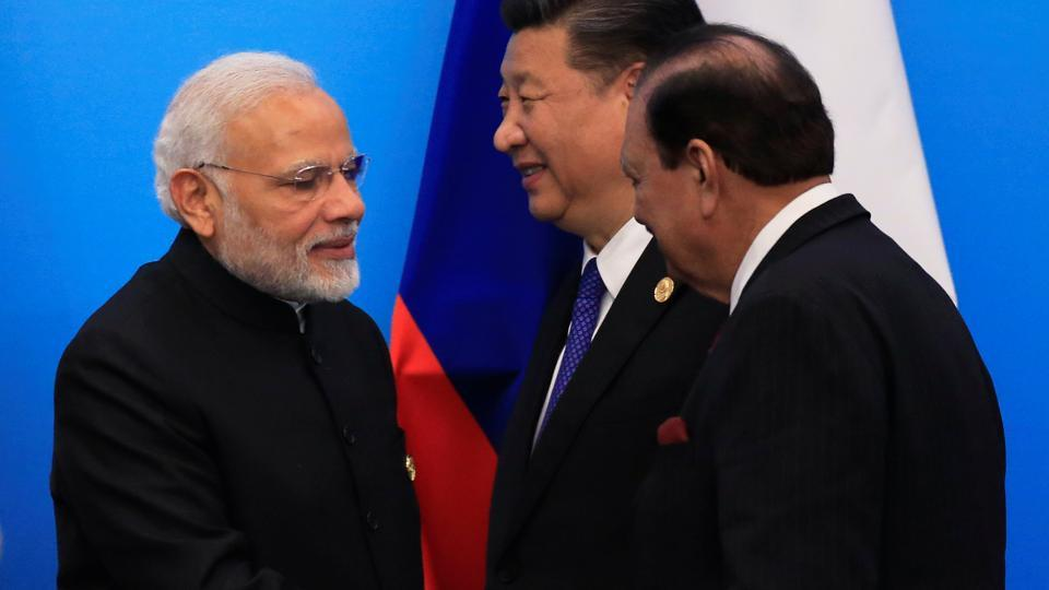 Pakistan's President Mamnoon Hussain shakes hands with Prime Minister Narendra Modi as China's President Xi Jinping walks behind them at a signing ceremony during Shanghai Cooperation Organization (SCO) summit in Qingdao, Shandong Province, China on June 10.