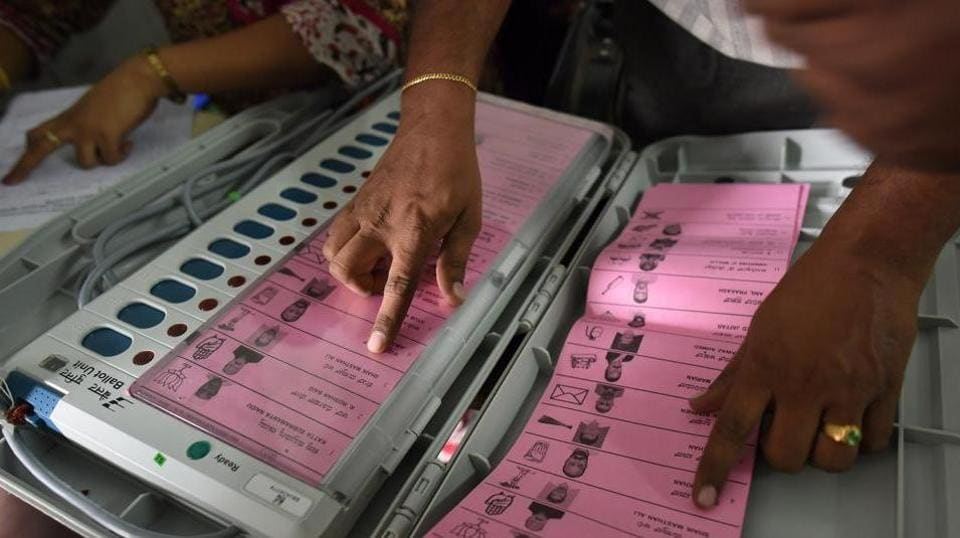 A polling staff tallies the candidates' names on the Electronic Voting Machines (EVM) before leaving for their respective booths, at the mustering centre in Kamlabai Girls High School in Bengaluru.