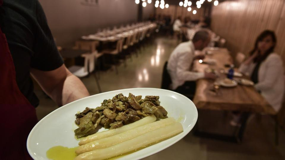 A cook holds a plate with white asparagus ready to be eaten, at a restaurant in Pamplona. Locals eat them by holding them with two fingers, upside down and above the head, and slowly bringing them down and into the mouth. The best asparaguses are said to melt at the touch of the tongue. (Alvaro Barrientos / AP)