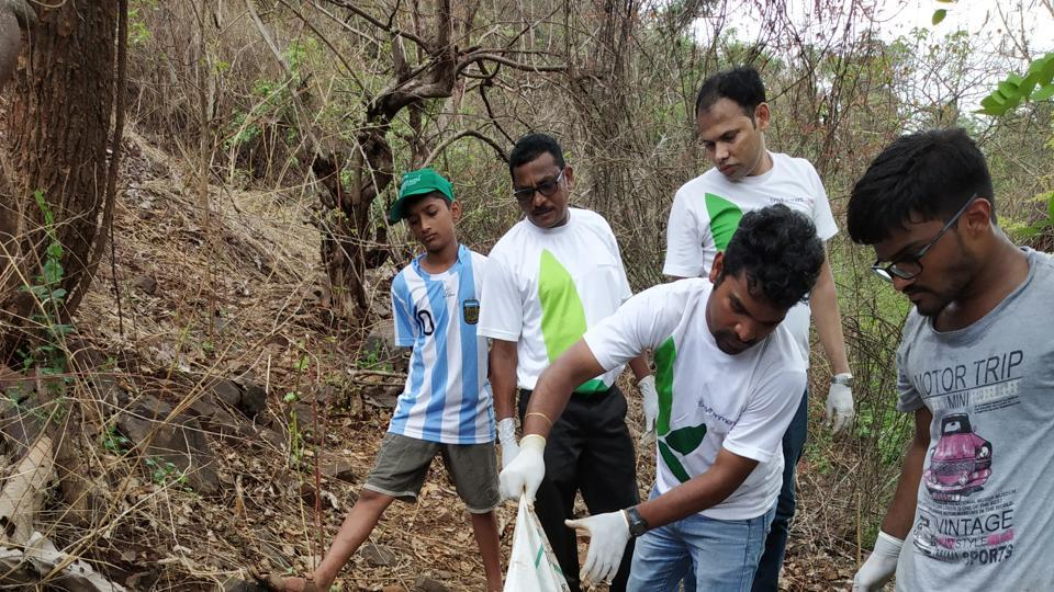 Volunteers during the clean-up drive at Palasdhari falls on Sunday.