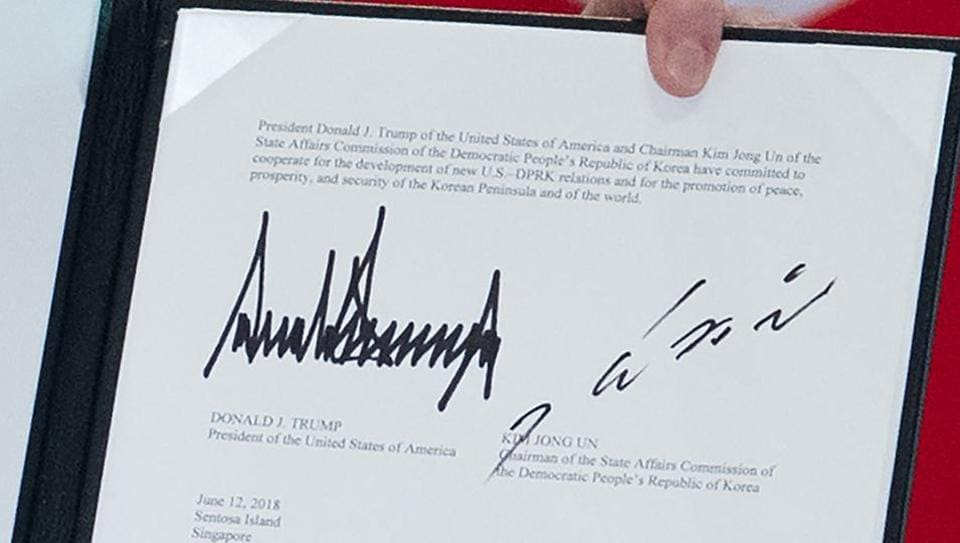 The signatures of US President Donald Trump (left) and North Korea's leader Kim Jong Un are seen on a document held up by Trump following a signing ceremony during their historic US-North Korea summit, at the Capella Hotel on Sentosa island in Singapore on June 12, 2018.