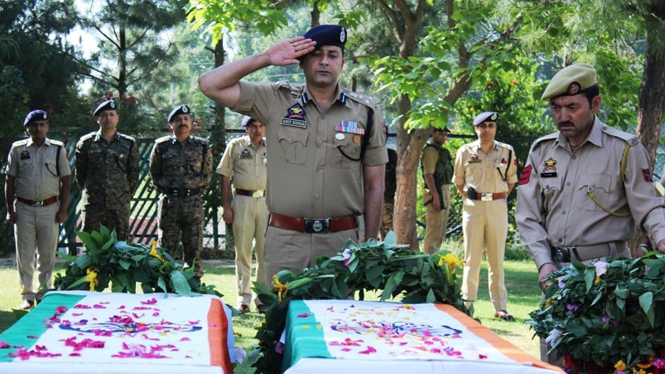 Security personnel pay tribute to slain J&K cops Ghulam Hassan and Ghulam Rasool in Pulwama on Tuesday.