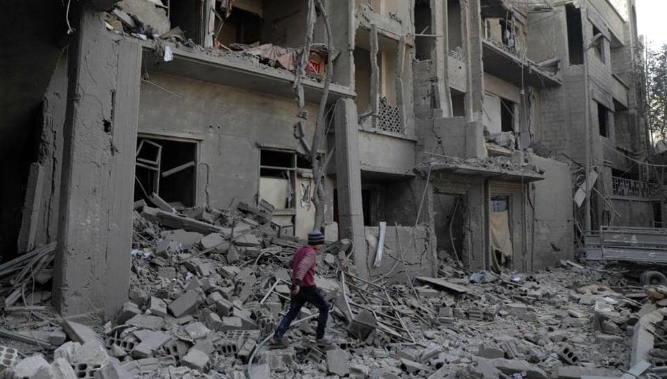 A Syrian boy walk past destruction following air strikes in the Eastern Ghouta rebel-held enclave of Douma, on the eastern outskirts of the capital Damascus on March 19, 2018.