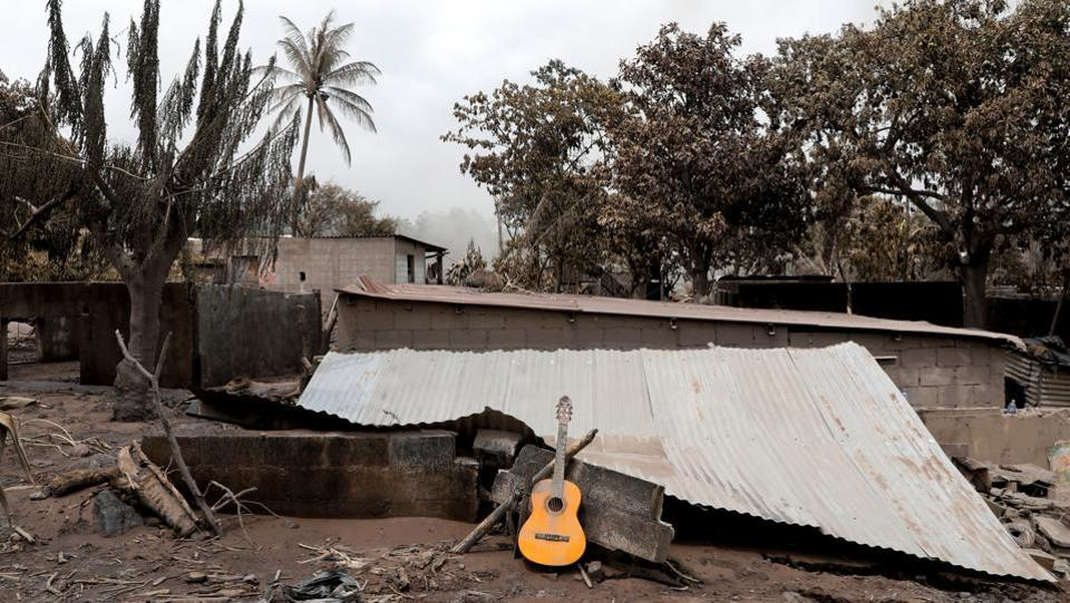 A guitar is seen on the roof of a damaged house. By the time most families in the worst-hit hamlets of El Rodeo and San Miguel de Los Lotes knew what was happening, they only had time to run, if that. (Carlos Jasso / REUTERS)