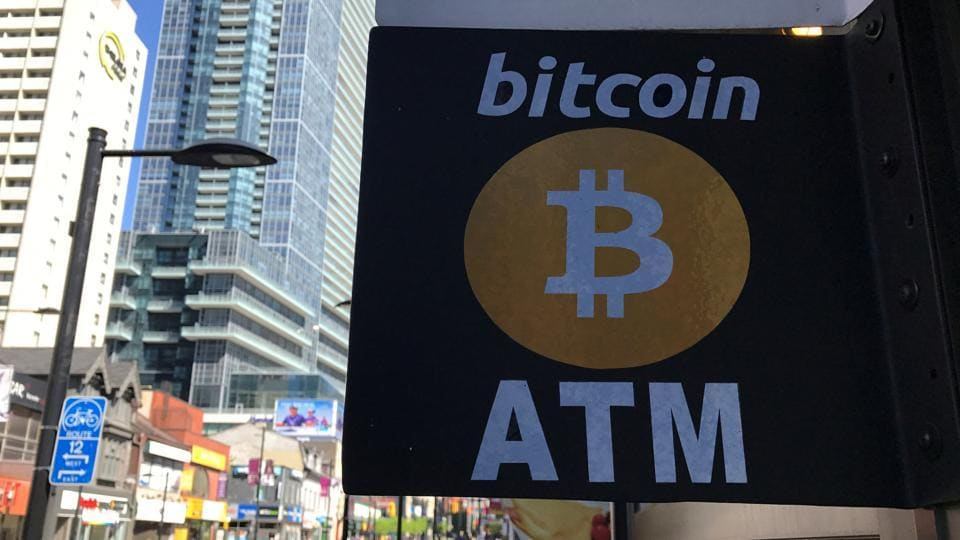 A sign is seen outside a business where a Bitcoin ATM is located in Toronto, Ontario, Canada.