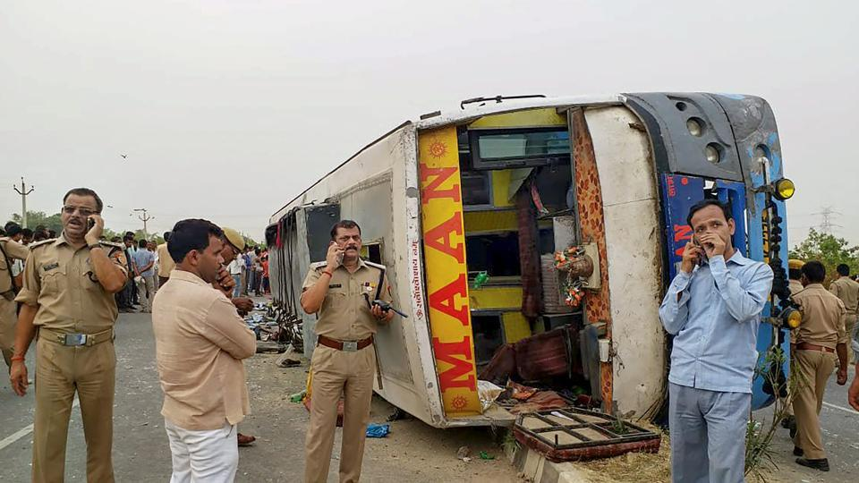Police personnel investigate the site where an allegedly speeding bus overturned after hitting a road divider in Mainpuri on Wednesday. More than a dozen people were killed and a dozen others injured when the private tourist bus lost control. It was travelling from Rajasthan's Jaipur to Farukkhabad in Uttar Pradesh when the accident occurred near Kiratpur village around 5am. (PTI)