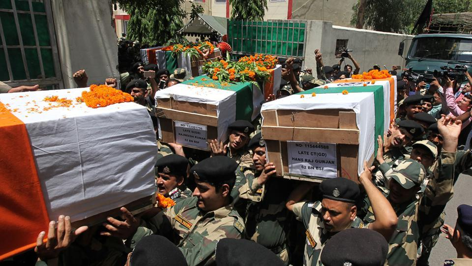 Border Security Force (BSF) officers carry the coffin of slain soldiers during a wreath-laying ceremony at the BSF headquarters in Jammu. Cross border firing left four BSF personnel dead on June 13 along the border dividing disputed Kashmir with the Pakistani province of Punjab. (AFP)