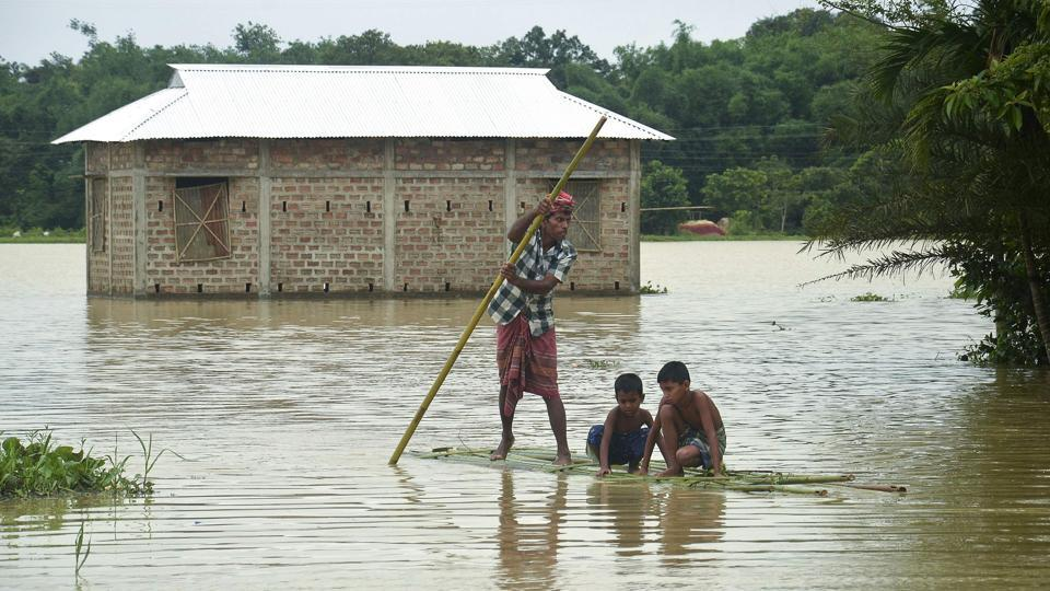 Villagers cross a flooded area on a bamboo raft at a village in Dharmanagar in Tripura.