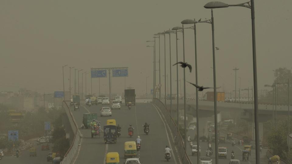 Vehicles ply slowly on a road as dust envelopes the sky over New Delhi, on Wednesday.