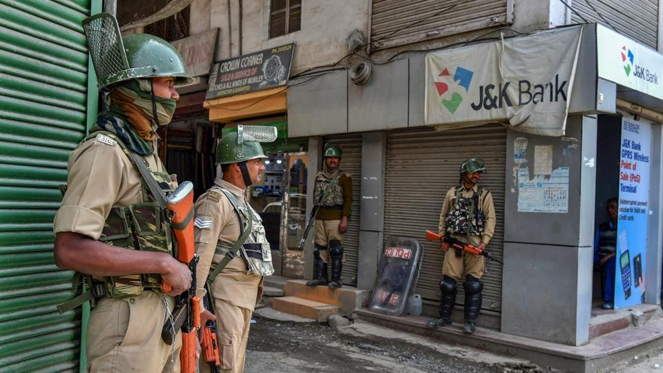 CRPF personnel stand guard near a shop on the first day of Ramadan, in Srinagar.