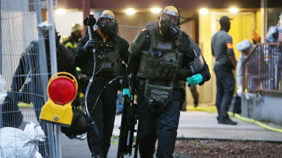 German police officers in protective gear leave an apartment building during an operation in Cologne.