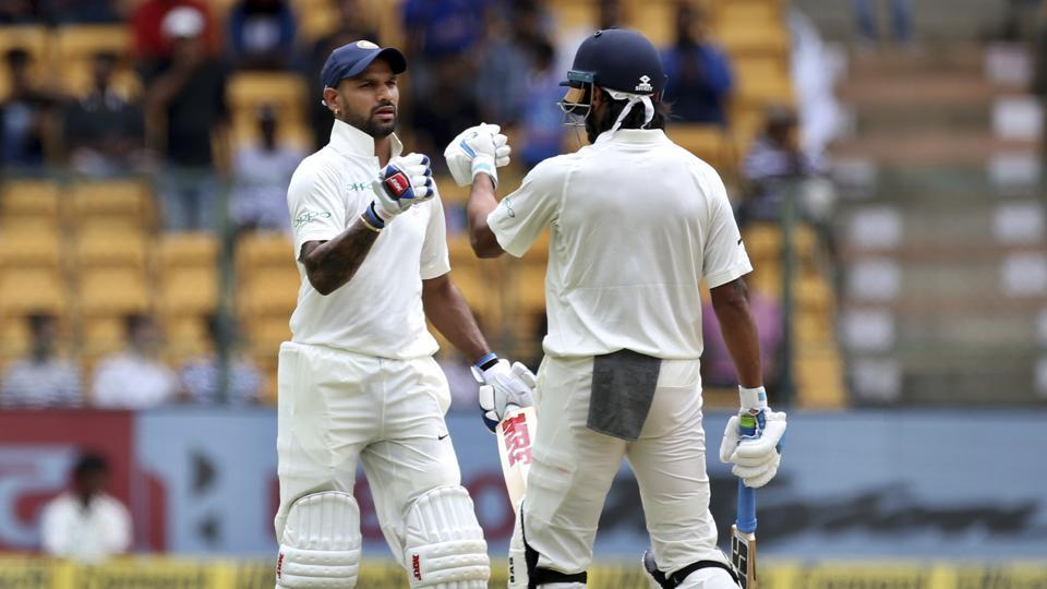 India's Murali Vijay, right, greets teammate Shikhar Dhawan, left, on hitting a boundary during the one-off cricket test match against Afghanistan in Bangalore.