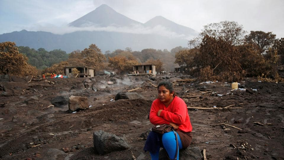 Milvia Vasquez observes an excavator removing ash from the site where she presumes her brothers are buried in an area affected from the eruption of Fuego volcano in San Miguel Los Lotes, in Escuintla, Guatemala. (Luis Echeverria / REUTERS)
