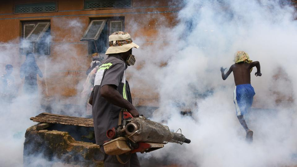 An agent of the National Institute of Public Hygene (INHP) carries out fumigation in the Anyama district of Abidjan, as part of the Ivory Coast's ongoing fight against dengue fever. (Sia Kambou / AFP)