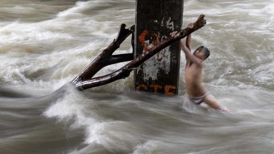 A boy holds a partially submerged branch as he plays in a swollen river caused by heavy rains under a bridge in Manila, Philippines. (Noel Celis / AFP)