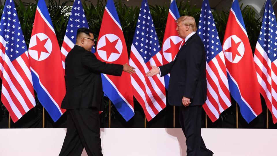 US President Donald Trump (R) and North Korea's leader Kim Jong Un (L) reach out to shake hands at the start of their historic US-North Korea summit, at the Capella Hotel on Sentosa island in Singapore. (Saul Loeb / AFP)