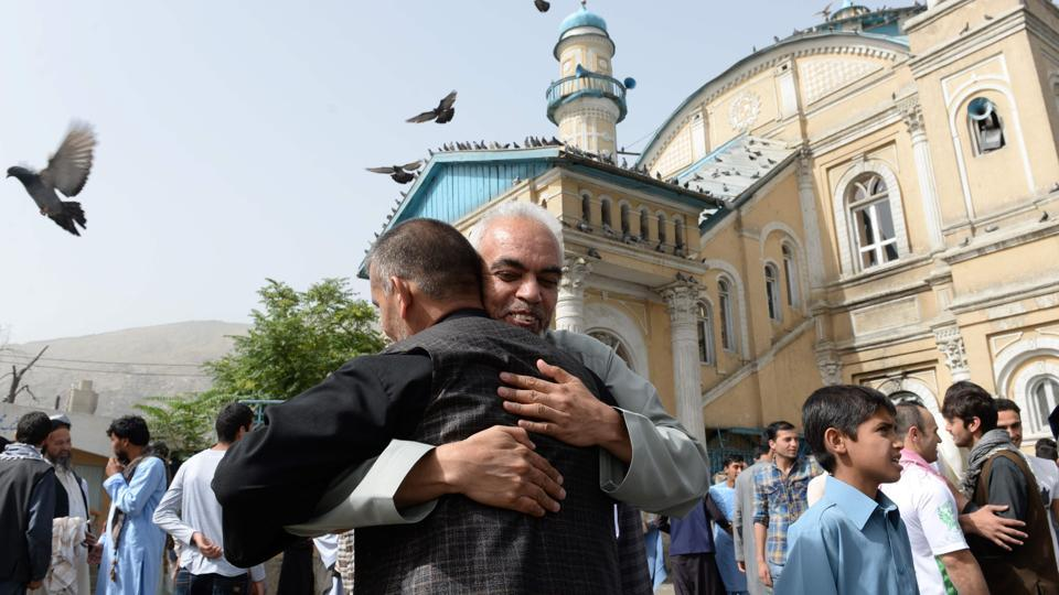 Afghan Muslims hug each other after offering prayers at the start of the Eid al-Fitr holiday which marks the end of Ramadan at the Shah-e Do Shamshira mosque in Kabul on Friday.