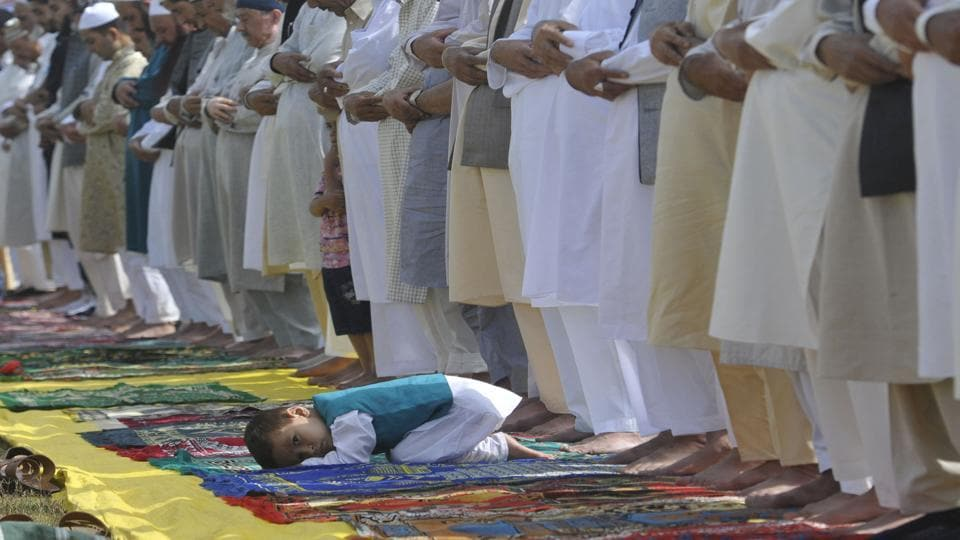 A little boy sneaks a glance as elders pray at an Eidgah in downtown Srinagar. (Waseem Andrabi / HT Photo)