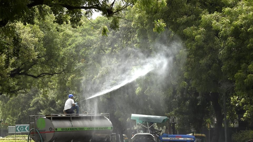 Employees of New Delhi Municipal Council horticulture department spray water over trees to curb air pollution by combating accumulated dust, near Vigyan Bhawan in New Delhi, on Friday.