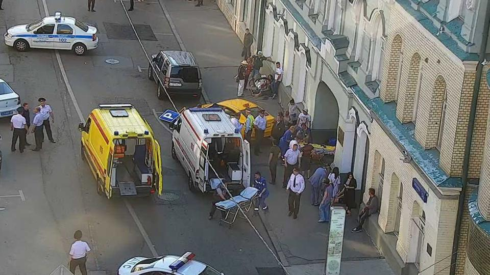 A handout CCTV picture released by the Moscow Municipal Traffic Regulation centre CODD shows Russian police officers and paramedics working at the scene, after a taxi drove into a crowd in Moscow.