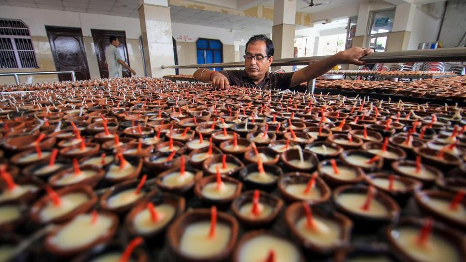 A person from the Kashmiri Pandit community arranges traditional earthen lamps at a Kheer Bhawani temple, during preparations for 'Jyeshthaashtami' annual congregation in Jammu. (PTI)