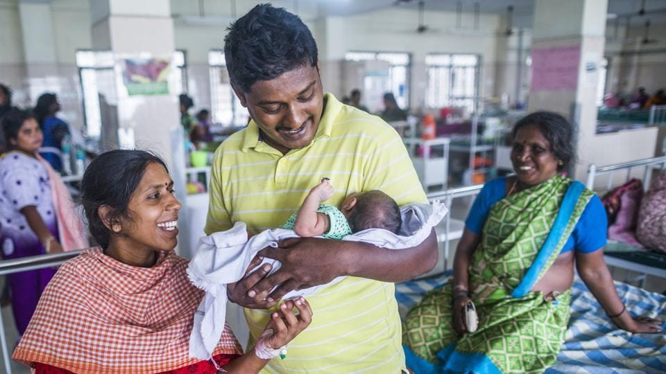 34-year-old Senthil Kumar cradles his three day old child from his wife Manimehalai's care for the first time at the Post Natal Ward of the Institute Of Obstetrics And Gynaecology And Govt. Hospital For Women And Children, in Egmore, Chennai on June 11, 2018. This series, also captured globally, seeks also to address a need for parental leave and its comparative lack. (Prashanth Vishwanathan / UNICEF)