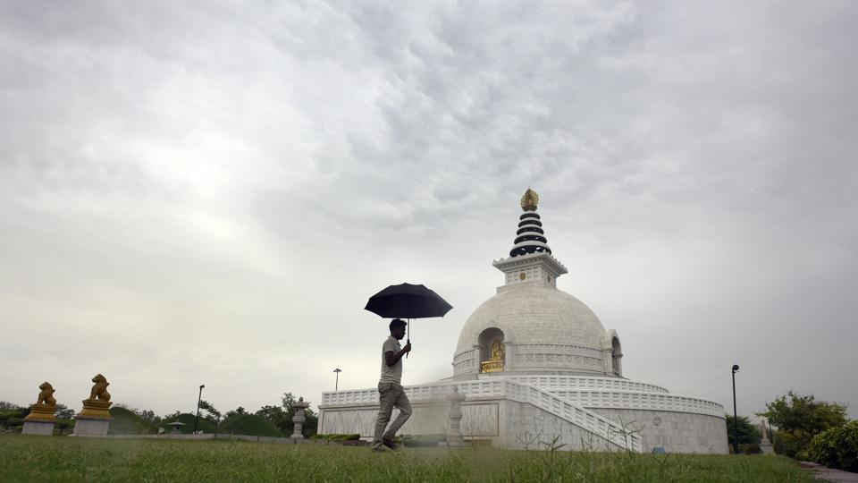 A man walking with an umbrella in a cloudy morning at replica of Shanti Stupa in New Delhi.