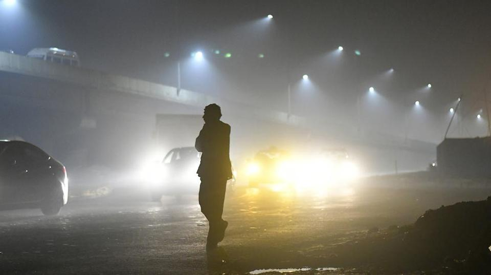 A pedestrian is silhouetted as traffic moves along a road shrouded in smog in New Delhi.