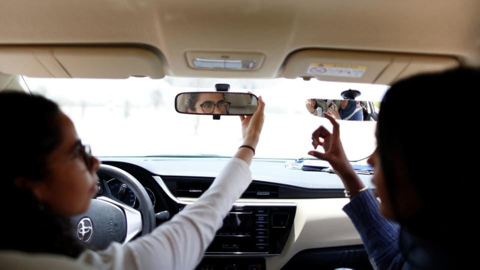 "Maria al-Faraj (L) adjusts a mirror during a driving lesson with instructor Ahlam al-Somali. In Amira Abdulgader's case, the day has already been laid out in her mind. She would like to go to her mother's house and take her for a ride. ""Just me and my mother, without anyone else,"" she said. (Ahmed Jadallah / REUTERS)"