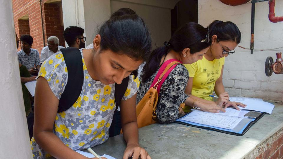 Students fill in application forms at North Campus after the first cut-off list for admissions to the colleges, under Delhi University, were declared in New Delhi on Tuesday, June 19, 2018. The admission under the first cut-off list will end on Thursday at 1pm for regular colleges and 7pm for evening colleges.
