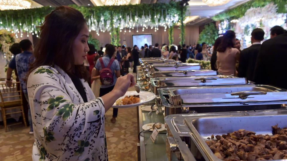 A guest puts food on her plate during a wedding at a hotel in Jakarta. Even as it struggles with poverty and malnutrition, the Southeast Asian nation bins more edible food per person than any other country except Saudi Arabia, according to an Economist Intelligence Unit survey last year. (Adek Berry / AFP)