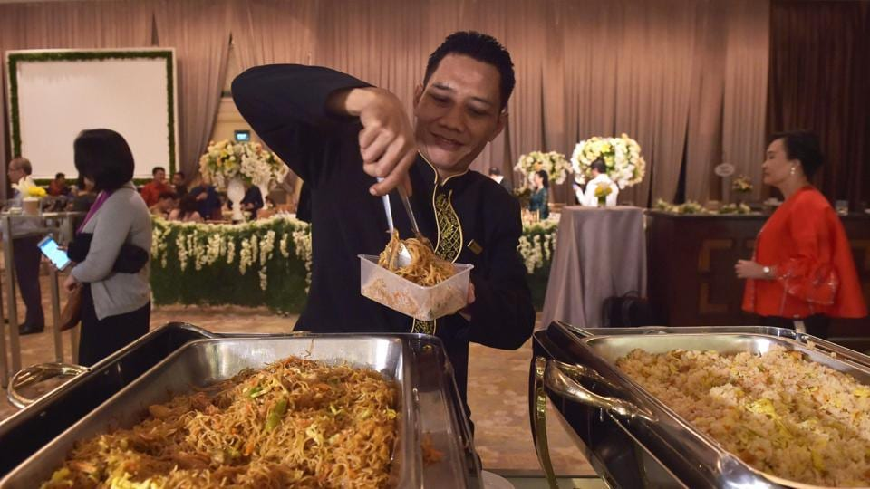 A waiter packs uneaten food for distribution after a wedding in Jakarta. Indonesia's 260 million citizens each throw out an average of almost 300 kilograms of food annually, ahead of the United States in third spot, the survey said. The country's food waste problem can be partly chalked up to local hospitality, which calls for ample helpings at all celebrations. (Adek Berry / AFP)