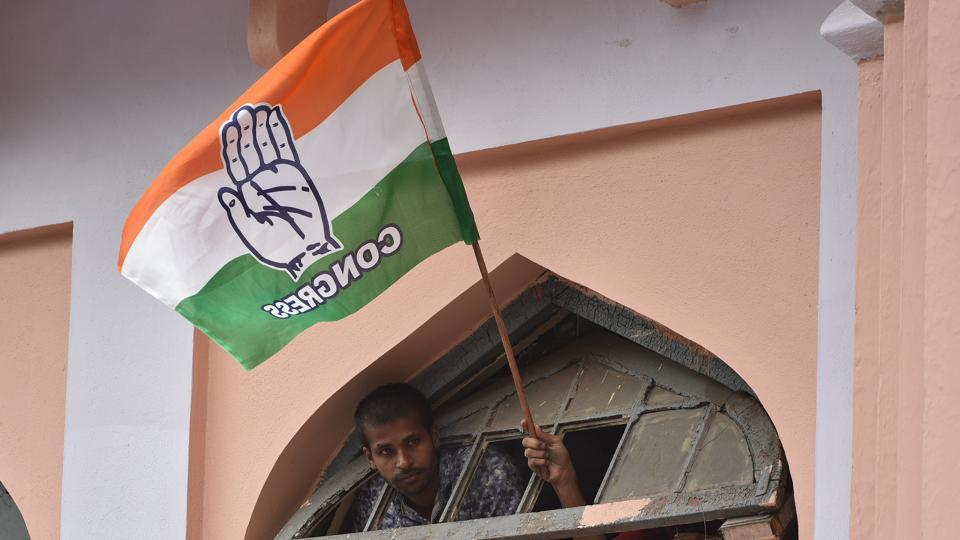 A Congress supporter waves party flag in Bengaluru.