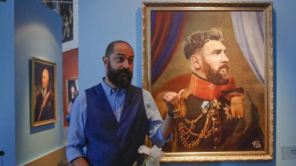 Italian artist Fabrizio Birimbelli stands next to his portrait of Argentine football star Lionel Messi. (AP)