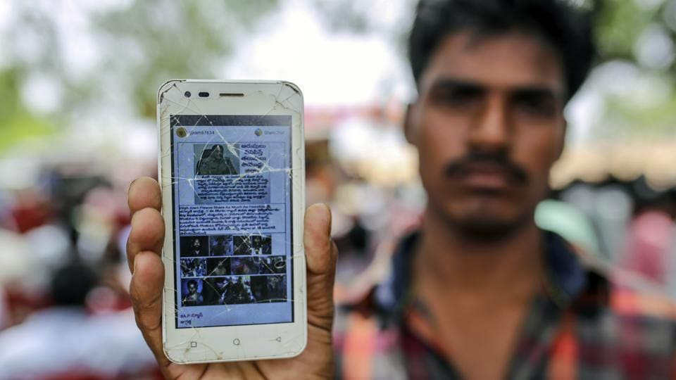 "In the village of Balgera, Thirumalesh Boya, a 21-year-old construction worker, holds up his battered smartphone to show a bogus message featuring the image of a policeman. ""High Alert Please Share As Much As Possible,"" it says, before warning of murderous gangs. Boya says he forwarded the message, before learning better from the police. (Dhiraj Singh / Bloomberg)"